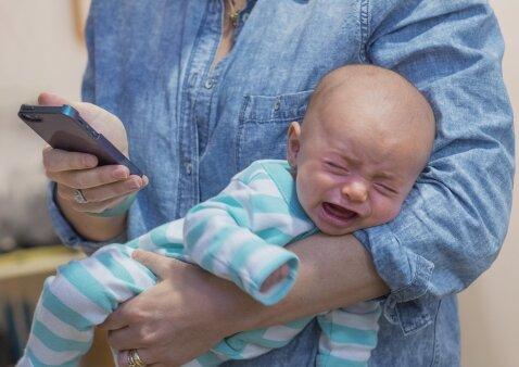 Kai tėvai vaikų akivaizdoje naršo savo telefonuose, vyksta kai kas negero