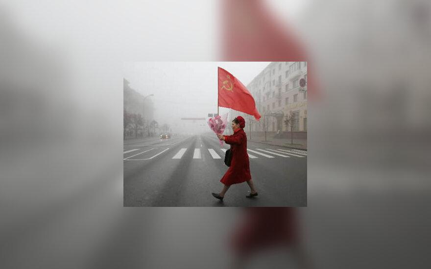 Moteris, nešina gėlėmis ir sovietų vėliava, eina Minsko gatve