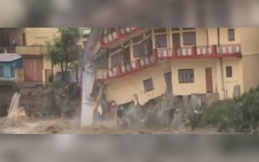 Liudininkai Indijoje užfiksavo, kaip potvynio vandenys nugriauna namą