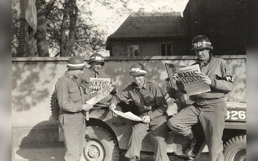 Amerykańscy żandarmi wojskowi czytają w gazecie o kapitulacji Niemiec, maj 1945 r./US Army personnel/US Army Military History Institute/Wikimedia