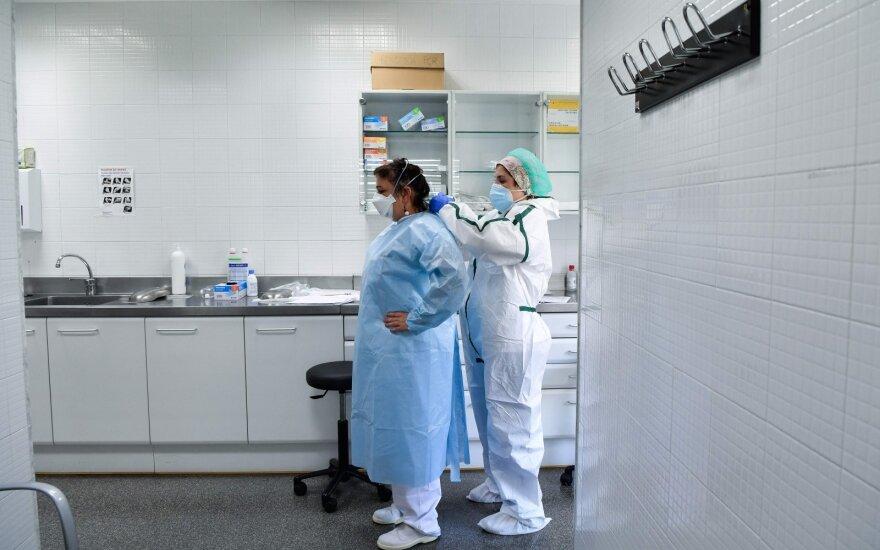 Sveikatos priežiūros darbuotojai ruošiasi rinkti mėginius naujo koronaviruso COVID-19 tyrimų kambaryje pirminės sveikatos priežiūros centre Barselonoje