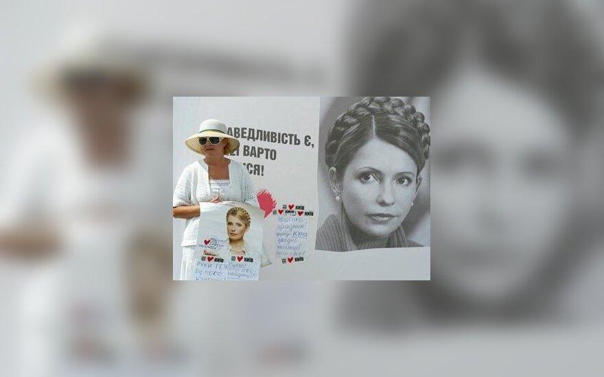 Moteris laiko Juliją Timošenko palaikantį plakatą Kijeve.