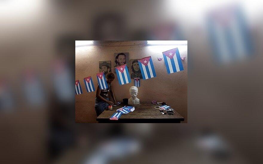"""Kubietė lanksto vėliavas stovėdama greta šalies prezidento Fidelio Castro ir Kubos didvyrių Camilo Cienfuegos bei Argentinoje gimusio Ernesto """"Che"""" Guevaros portretų."""