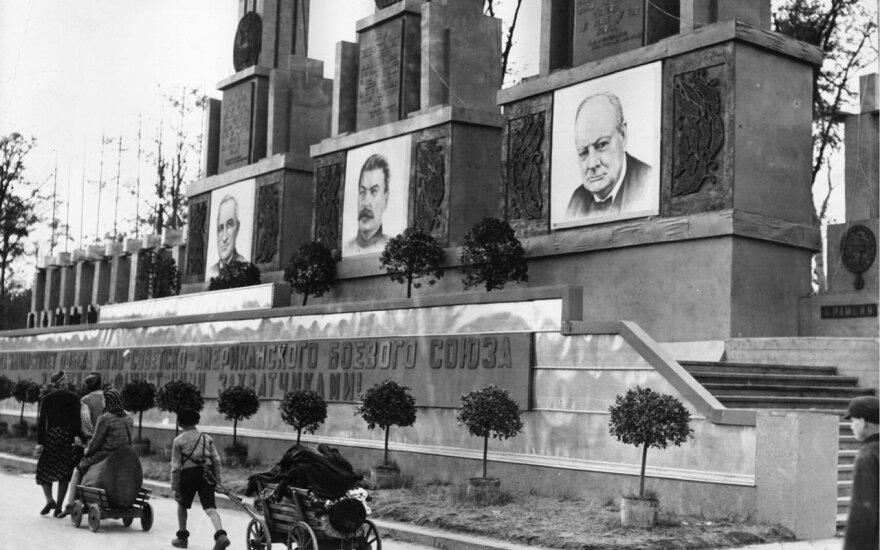 Sąjungininkų vadų portretais papuoštas monumentas. Prie jo – namus praradę vokiečių pabėgėliai. Berlynas. 1945 m. liepa.