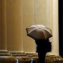 Moteris po skėčiu dengiasi nuo lietaus