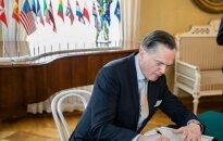 Ambassador at Large, H.E. Eitvidas Bajarūnas signs the document in Helsinki