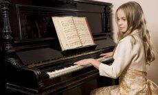 Mergaitė groja pianinu