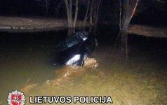Sprukdamas nuo policijos BMW vairuotojas su automobiliu atsidūrė upelyje