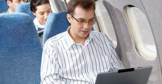 Vyras naudojasi kompiuteriu skrydžio metu