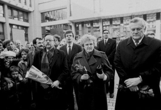 Prie LR Aukščiausiosios Tarybos rūmų LR Aukščiausiosios Tarybos-Atkuriamojo Seimo deputatai: LR Aukščiausiosios Tarybos-Atkuriamojo Seimo pirmininkas Vytautas Landsbergis, Kazimiera Danutė Prunskienė ir Algirdas Mykolas Brazauskas; už jų kairėje Kovo 11-osios Akto signataras Romualdas Ozolas; kiek toliau viduryje – Sąjūdžio Seimo Tarybos narys Algirdas Kaušpėdas