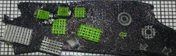 7 pav. Įvairių formų ir spalvų mikrodariniai iš PLA ant milimetrinio popieriaus, suformuoti 3D spausdintuvu ir vėliau apdirbti femtosekundine šviesos gija – išpjaunamos įvairios formos, pragręžiamos skylės, įpjaunami mikrogrioveliai.