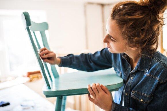 Mergina taiso seną kėdę