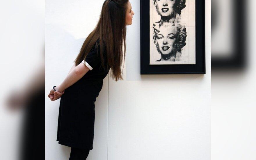 Moteris apžiūrinėja A.Warholo paveikslą