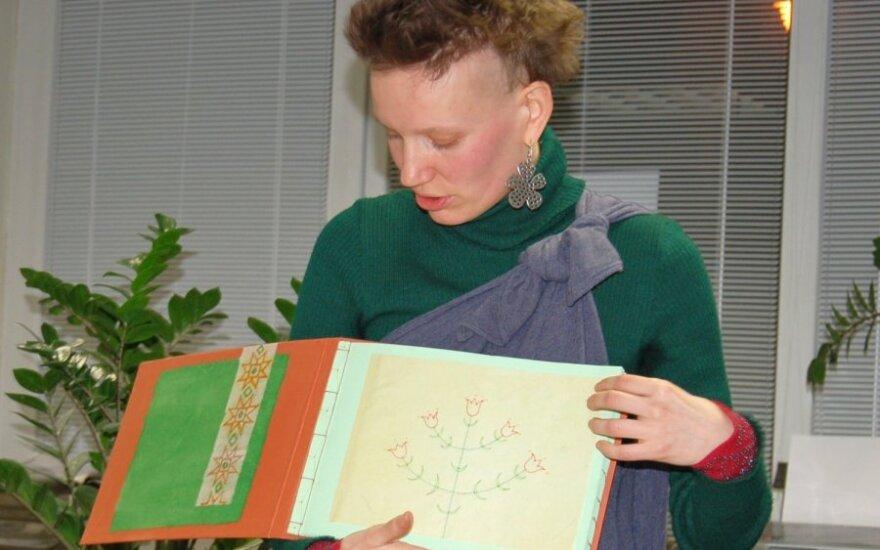 Menininkė Monika rodo pačios susiuvinėtą foto albumą