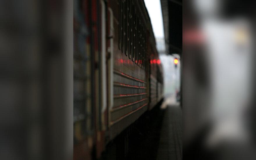 Šviesoforo signalas atsispindi traukinio paviršiuje
