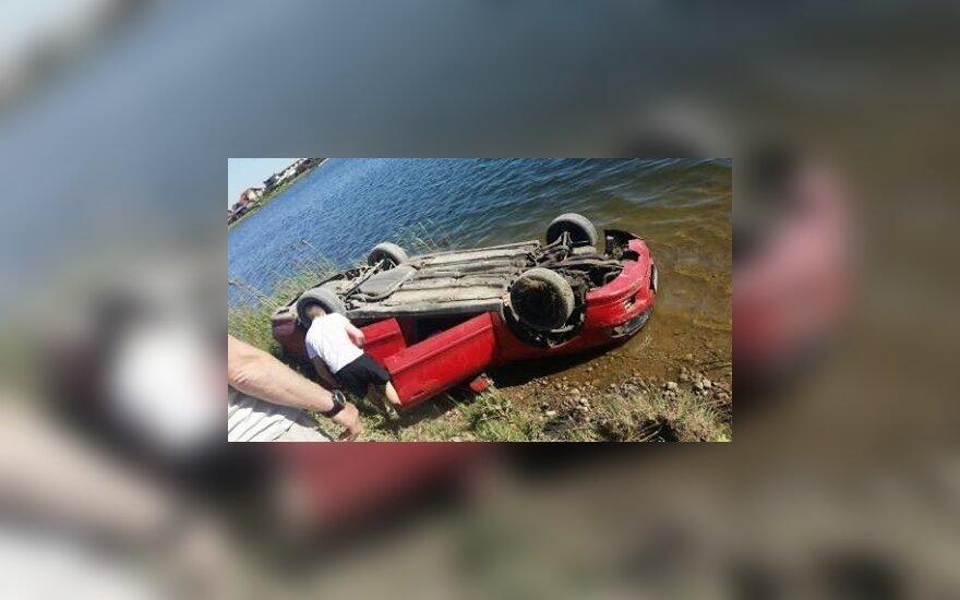 Klaipėdos rajone ant stogo virtęs automobilis įkrito į karjerą
