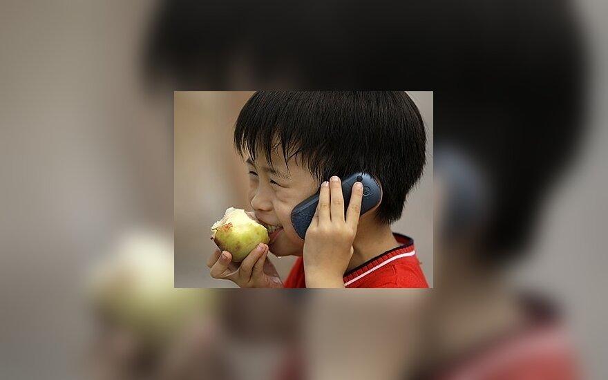 Kinų berniukas valgo obuolį ir kalba mobiliuoju telefonu. Re