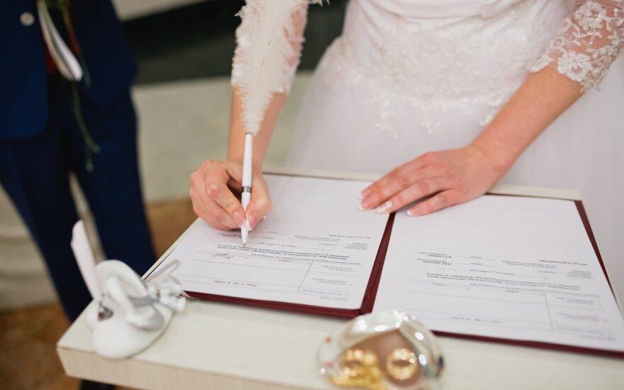 Moteris pasirašo vedybų dokumetus
