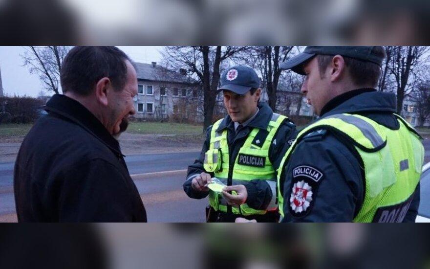 Kelių policijos patruliai dalija atšvaitus