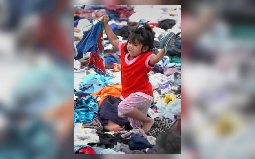 Mergaitė renkasi drabužėlius, gautus iš labdaros cunamio aukoms. Tailandas.