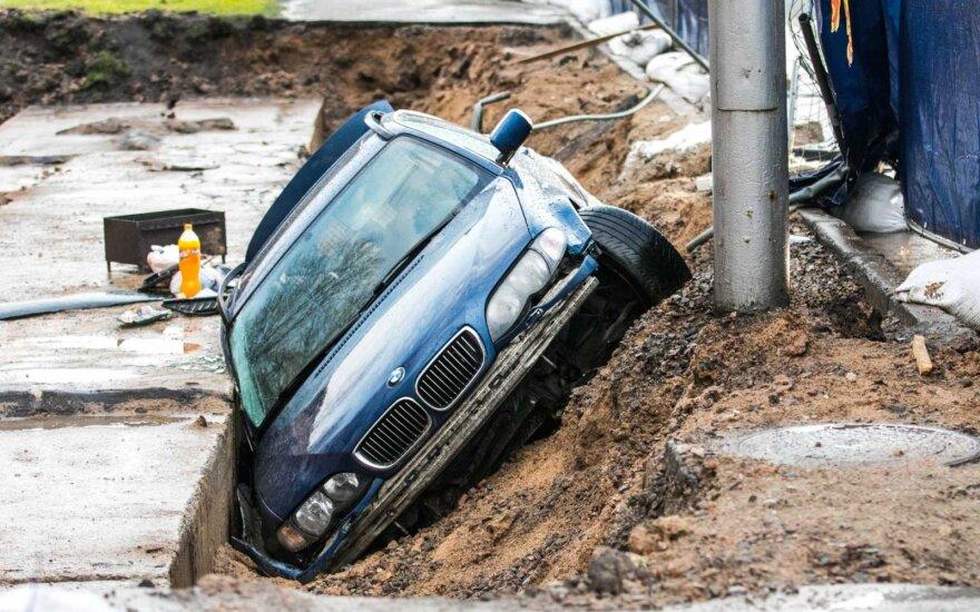 Taip sugeba ne kiekvienas: BMW nuvertė tvorą ir įkrito į renovuojamo vamzdyno tranšėją