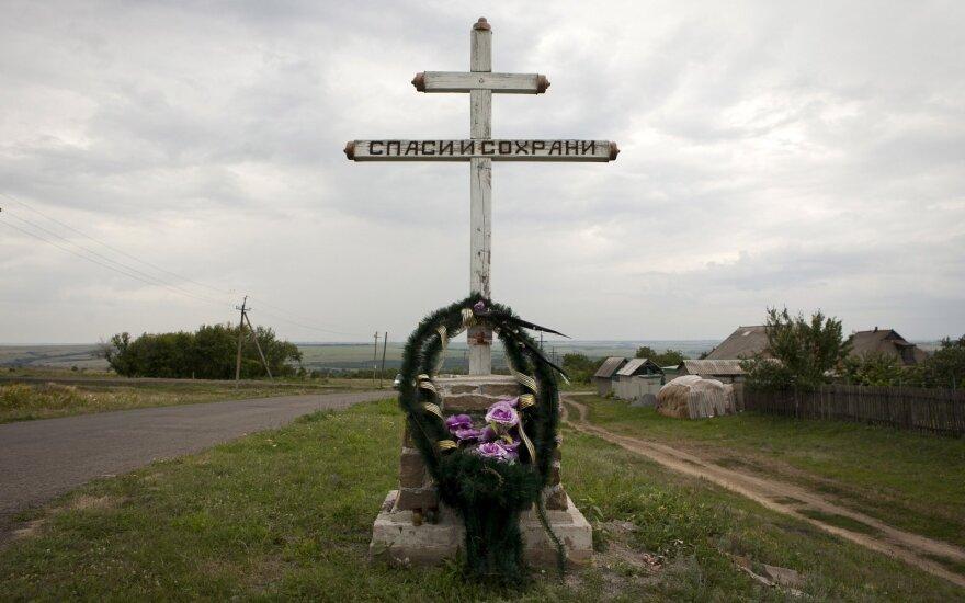 MH17 tragedijos vietoje žmonės neša vainikus ir stato kryžius