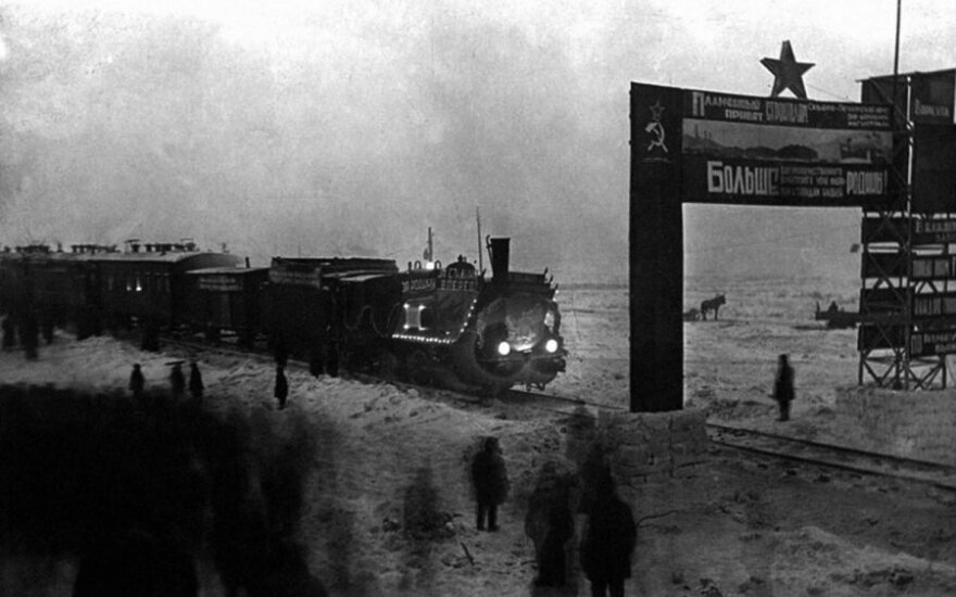 """""""Iškilmingai pasitinkamas pirmasis garvežys, atvykęs į Vorkutą"""". Garvežys išpuoštas pasityčiojamaisiais užrašais: """"Už Tėvynę, už Staliną – pirmyn!"""" Tikrovė tokia – garvežio pasitikti suvaryti Vorkutos lagerio nuteistieji fotografo nuotraukoje specialiai p"""