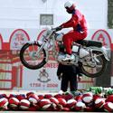 Indijos kareivio pasirodymas su motociklu virš savo kolegų.