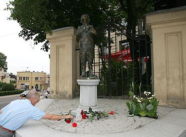 Vyras deda gėles prie paminklo Romain Gary