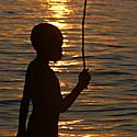 Berniukas saulėlydžio fone
