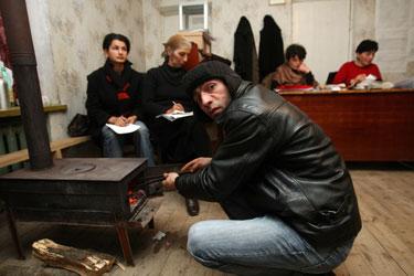 Gruzijoje rikimų komisijos narys šildosi prie krosnies