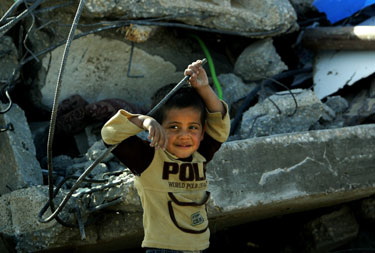 Palestinietis berniukas stovi prie savo šeimos namų griuvėsių.