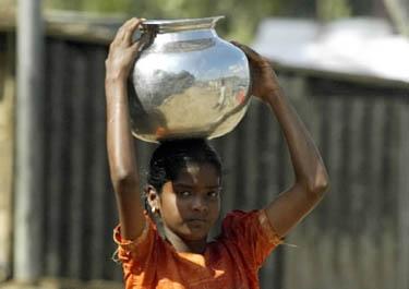 Indė, pergyvenusi cunamio siausmą, neša geriamo vandens ąsotį.