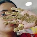Jaunoji Bangladešo gyventoja rodo chna dažais išmargintą ranką.