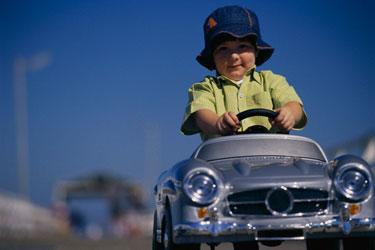 Berniukas važiuoja žaisliniu automobiliu